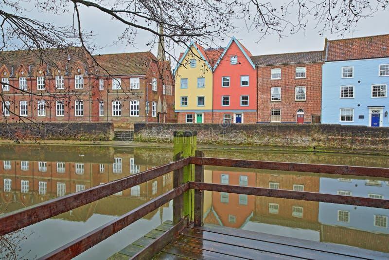 El río Wensum de la orilla con reflexiones de las casas coloridas y la torre y el chapitel de la catedral fotos de archivo
