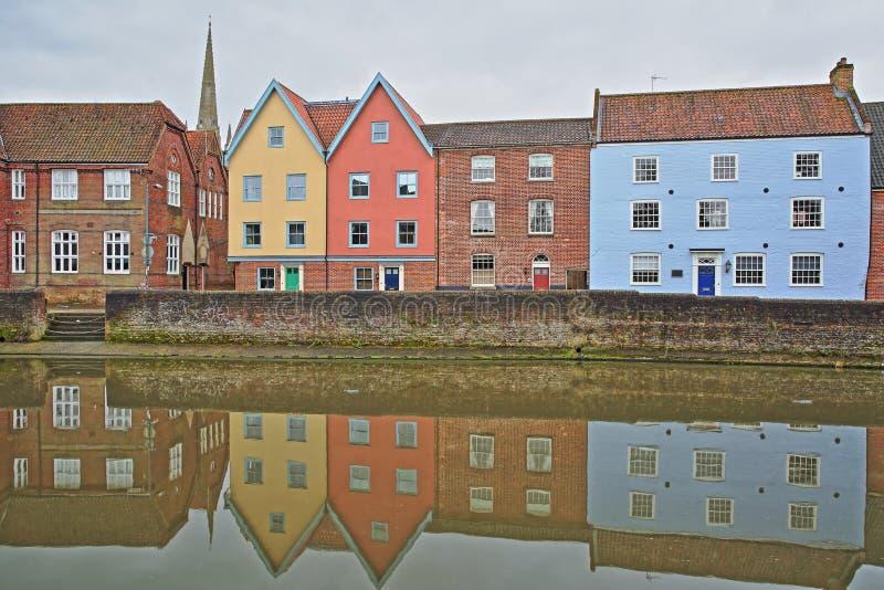 El río Wensum de la orilla con reflexiones de las casas coloridas y la torre y el chapitel de la catedral imágenes de archivo libres de regalías