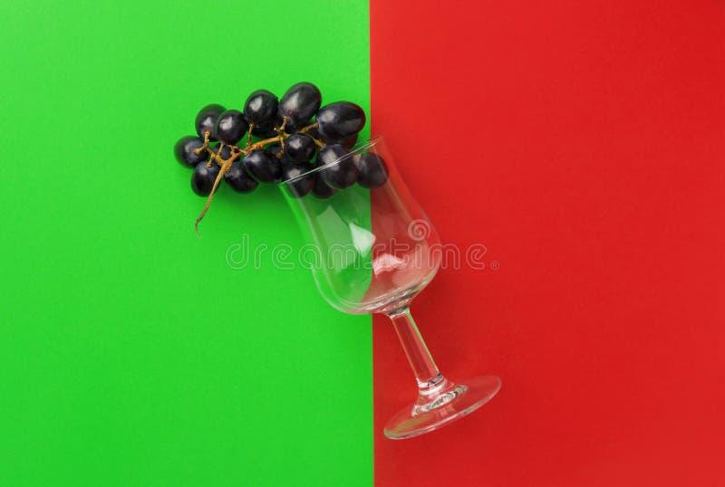 El racimo de luna cae las uvas púrpuras oscuras que imitan el vino en vidrio en fondo verde rojo del duotone Producción de vino fotos de archivo