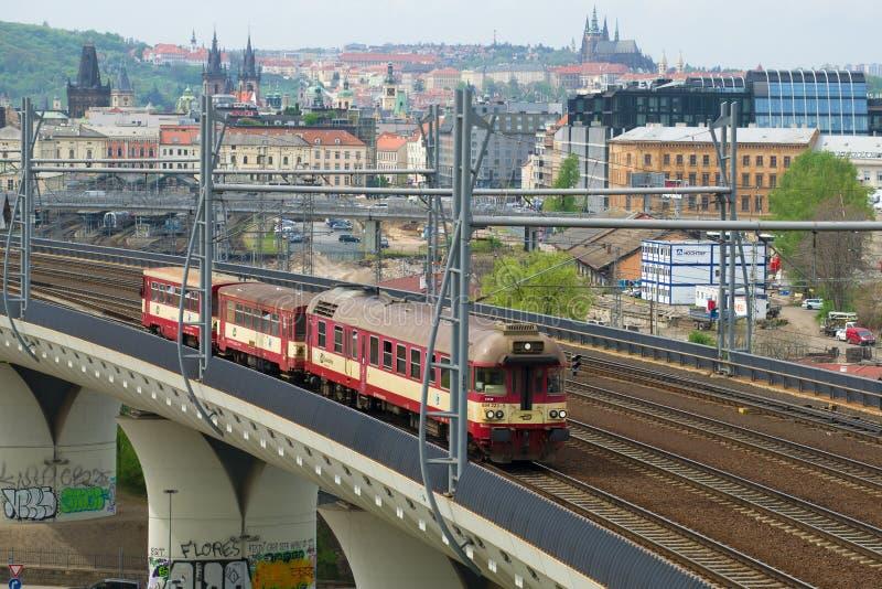 El railcar con los carros pasa el tren local en un viaducto ferroviario praga imagenes de archivo