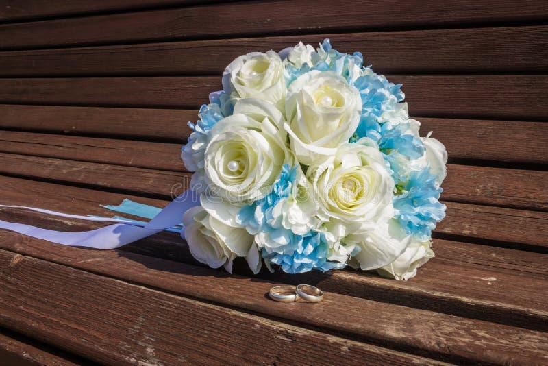 El ramo artificial de rosas blancas y los anillos de bodas están en el banco fotografía de archivo