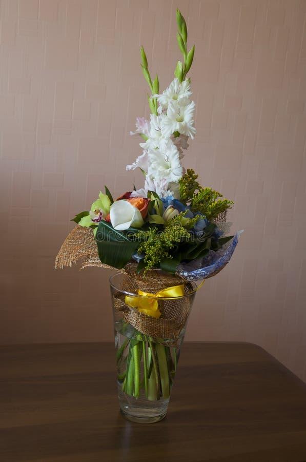 El ramo colorido con las flores tales como el gladiolo, orqu?dea, rosas, calas, mimosa se est? colocando en el florero grande de  imagen de archivo