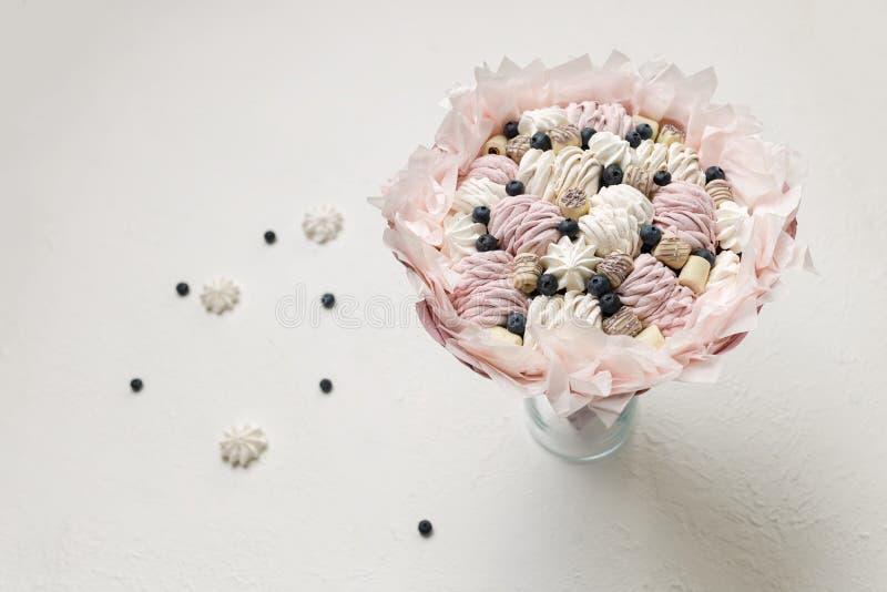 El ramo de dulces se coloca en un florero de cristal en un fondo blanco, espacio de la copia fotos de archivo
