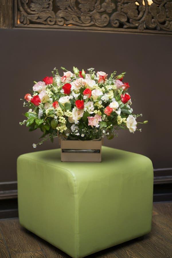 El ramo de flores en una caja de madera cuesta en un taburete rellenado verde foto de archivo libre de regalías