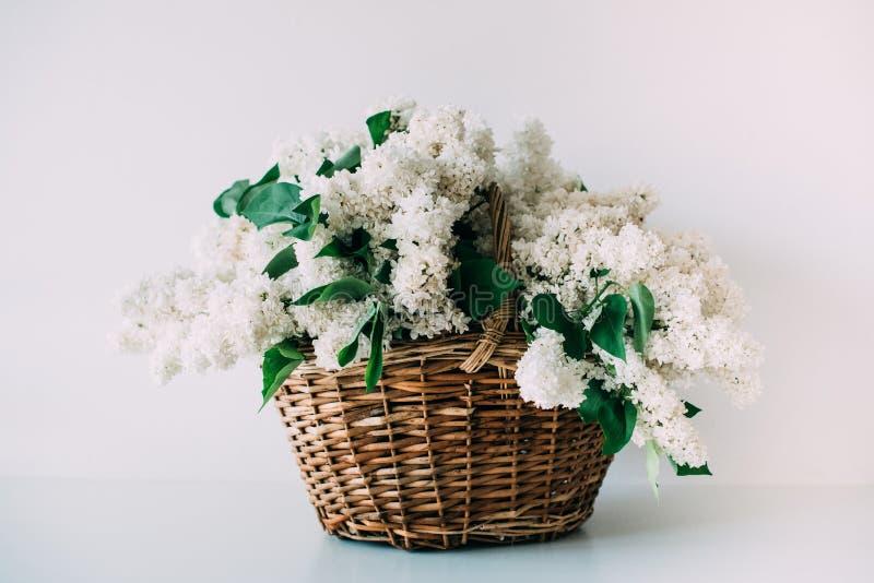 El ramo de lila blanca fresca florece en cesta de mimbre en de madera fotografía de archivo libre de regalías