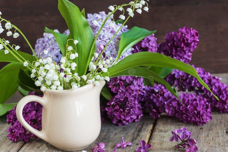El ramo de lirios del valle y de la lila florece foto de archivo