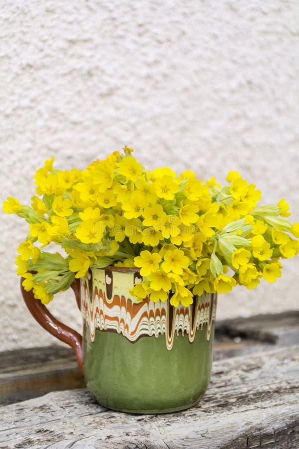 El ramo de primaveras salvajes hermosas florece en una taza de la arcilla del vintage fotos de archivo