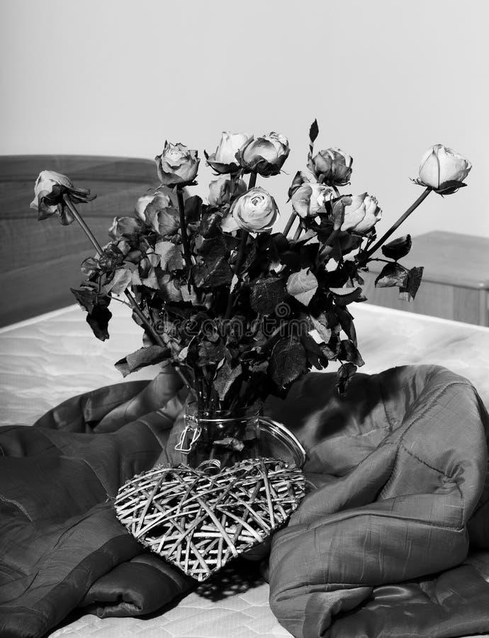 El ramo de rosas anaranjadas en florero transparente con el corazón gris decorativo de la tarjeta del día de San Valentín se colo imagen de archivo libre de regalías