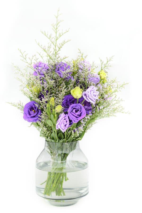 el ramo de rosas violetas en el florero de cristal en blanco aisló b imagen de archivo