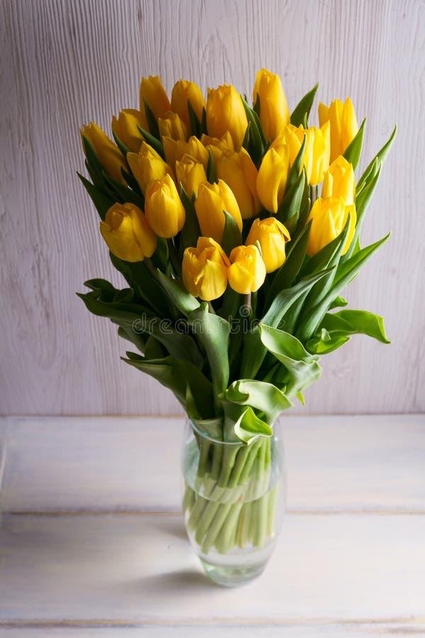 El ramo de tulipanes de la primavera florece en florero en fondo negro Tulipanes amarillos imágenes de archivo libres de regalías