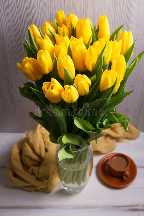 El ramo de tulipanes de la primavera florece en florero en fondo negro Tulipanes amarillos imagenes de archivo