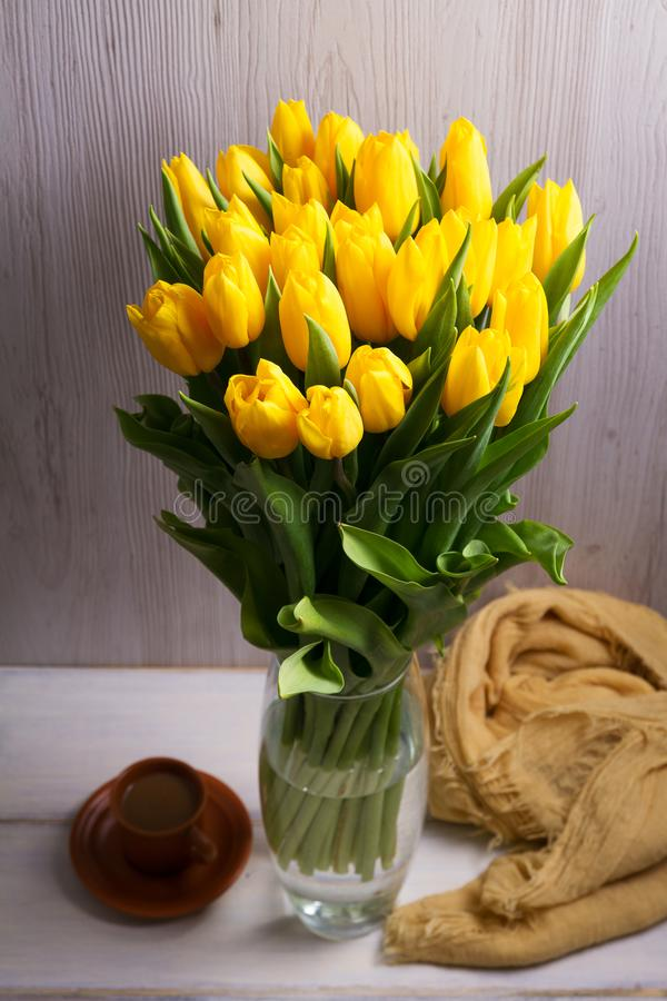 El ramo de tulipanes de la primavera florece en florero en fondo negro Tulipanes amarillos fotografía de archivo