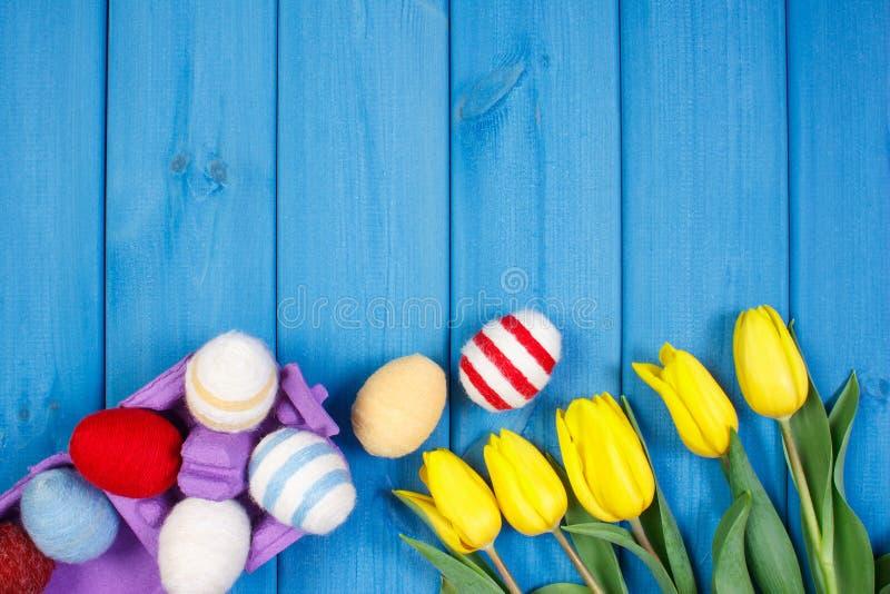 El ramo de tulipanes y de huevos de Pascua frescos envolvió la secuencia de lana, decoración de Pascua, espacio de la copia para  imágenes de archivo libres de regalías