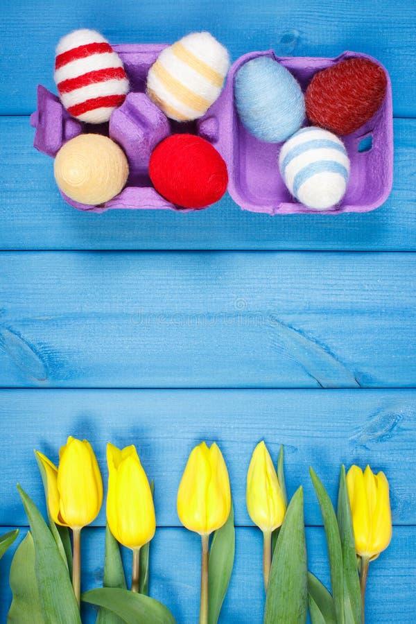 El ramo de tulipanes y de huevos de Pascua frescos envolvió la secuencia de lana, decoración de Pascua, espacio de la copia para  imagen de archivo libre de regalías
