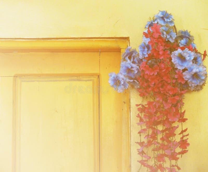 El ramo hermoso de flores por la puerta de madera con color suave del foco filtró el fondo usado como plantilla, estilo del vinta imágenes de archivo libres de regalías