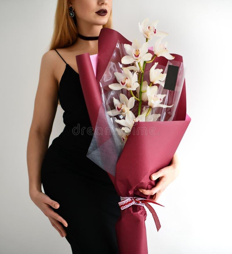 El ramo hermoso del control de la mujer de orquídea rosada blanca florece en gris imagen de archivo