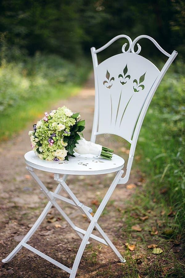 El ramo nupcial de flores blancas y de verdor está en una silla del vintage fotografía de archivo libre de regalías