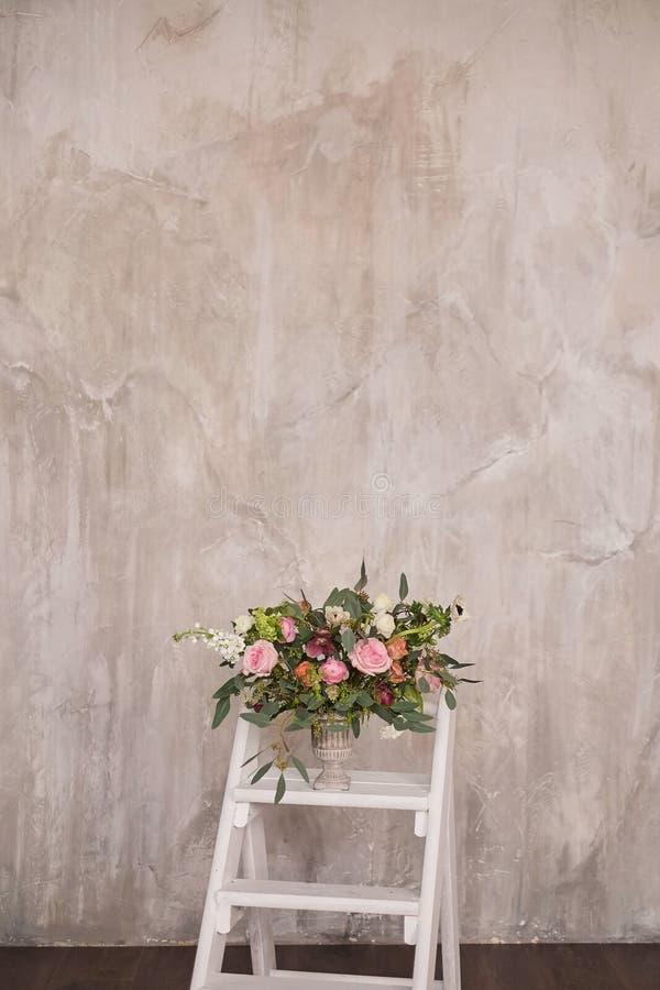 El ramo nupcial del otoño de flores se coloca en la escalera de mano blanca de la escalera imagenes de archivo