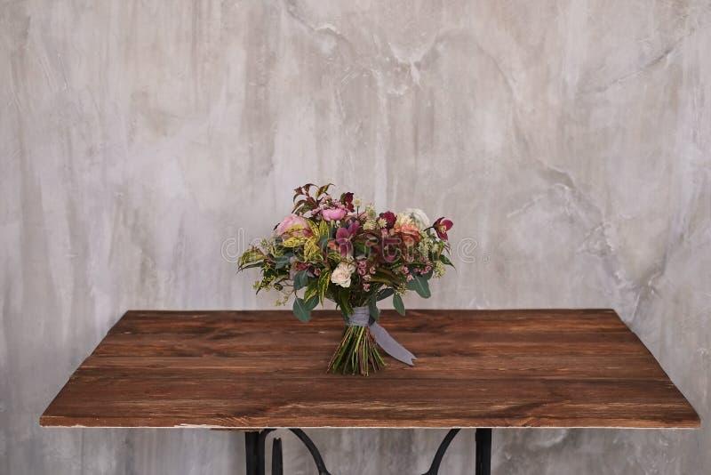 El ramo nupcial del otoño de flores se coloca en una tabla de madera marrón fotos de archivo