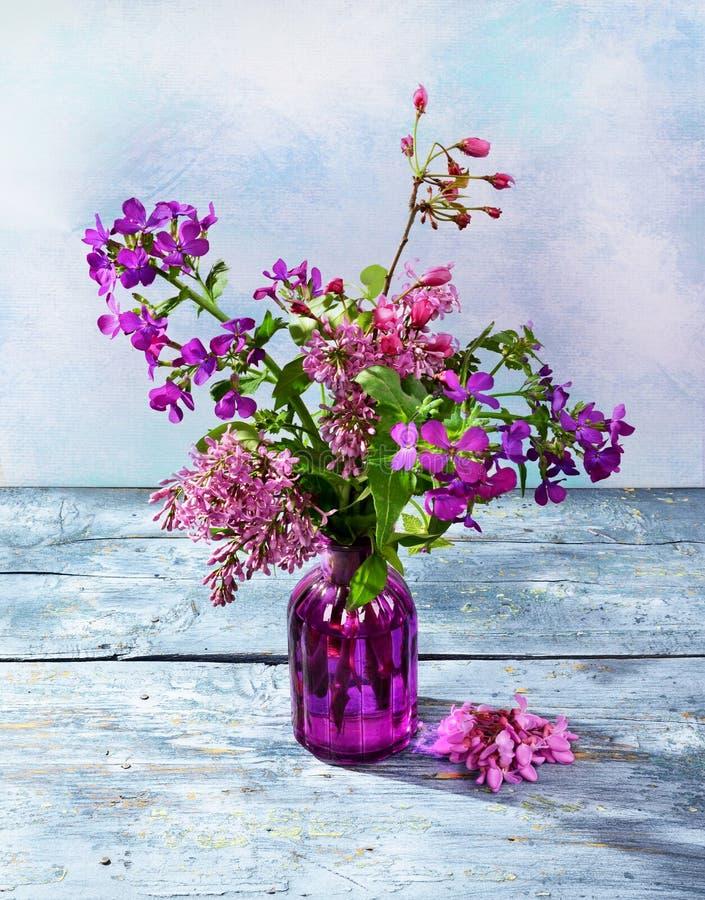 El ramo púrpura de la primavera florece en un florero de cristal imagen de archivo