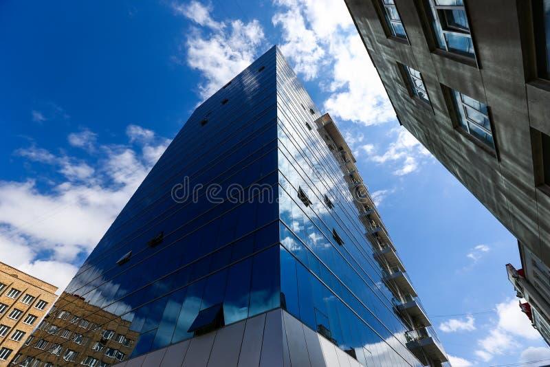 El rascacielos del centro de negocios A con los cristales azules sube a las nubes Edificio del alto cargo imagenes de archivo