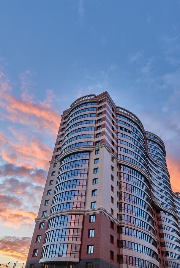 El rascacielos moderno alto con una forma única tiró en la puesta del sol, espacio de la copia arriba foto de archivo