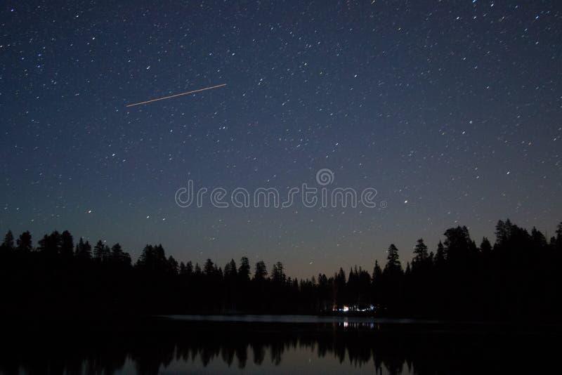 El rastro de un avión sobre un lago de la luz de las estrellas fotografía de archivo