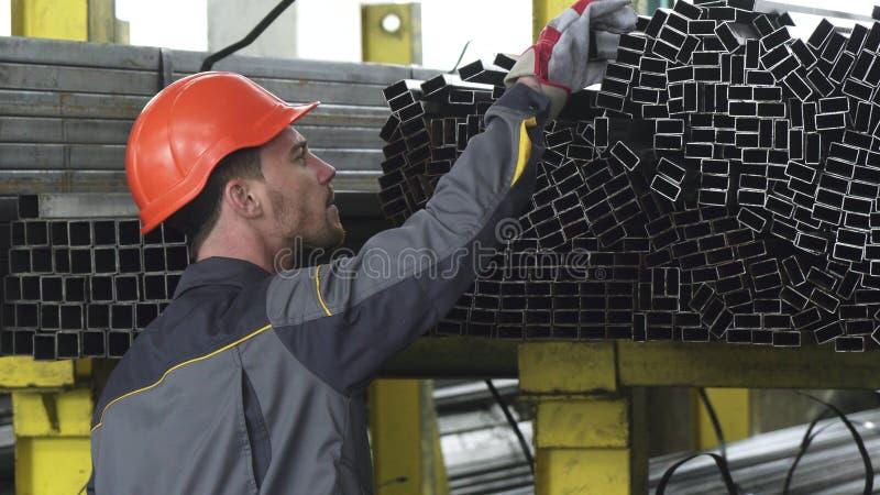 El Rearview tiró de los tubos de organización de un metal del trabajador de sexo masculino del almacenamiento en el estante fotografía de archivo