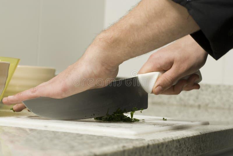 El rebanar de las manos del cocinero fotos de archivo