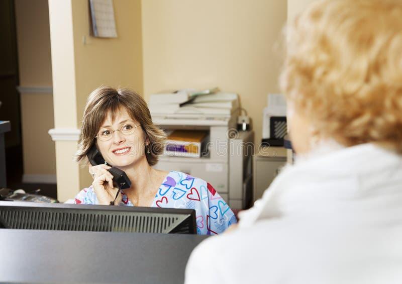El recepcionista saluda al paciente fotos de archivo
