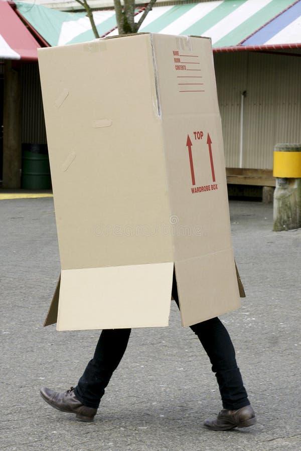 El recorrer de la caja de cartón del hombre foto de archivo