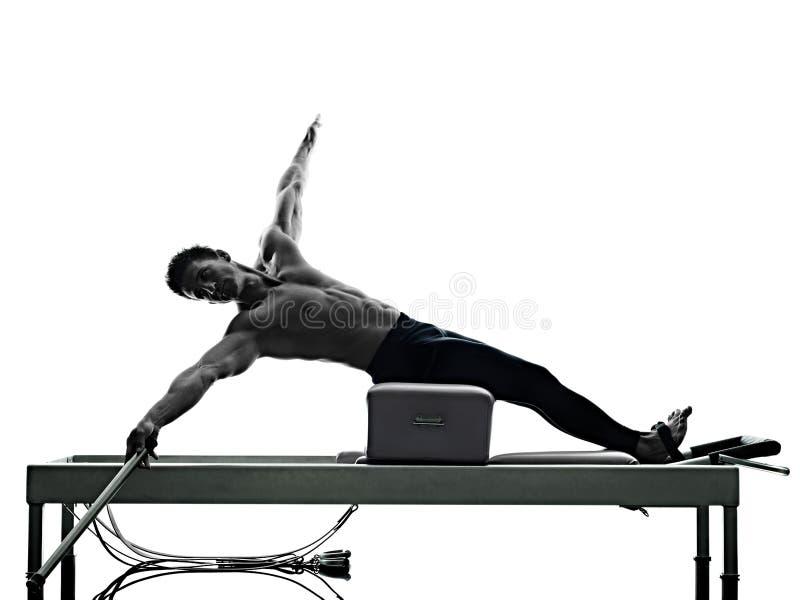 El reformador de los pilates del hombre ejercita aptitud aislado foto de archivo