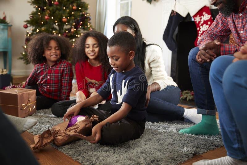 El regalo de la abertura del hijo como familia multi de la generación celebra la Navidad en casa junta imagen de archivo libre de regalías