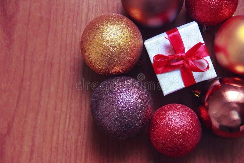 El regalo del Año Nuevo en una caja blanca con un arco rojo y los juguetes brillantes multicolores para el árbol de navidad foto de archivo libre de regalías