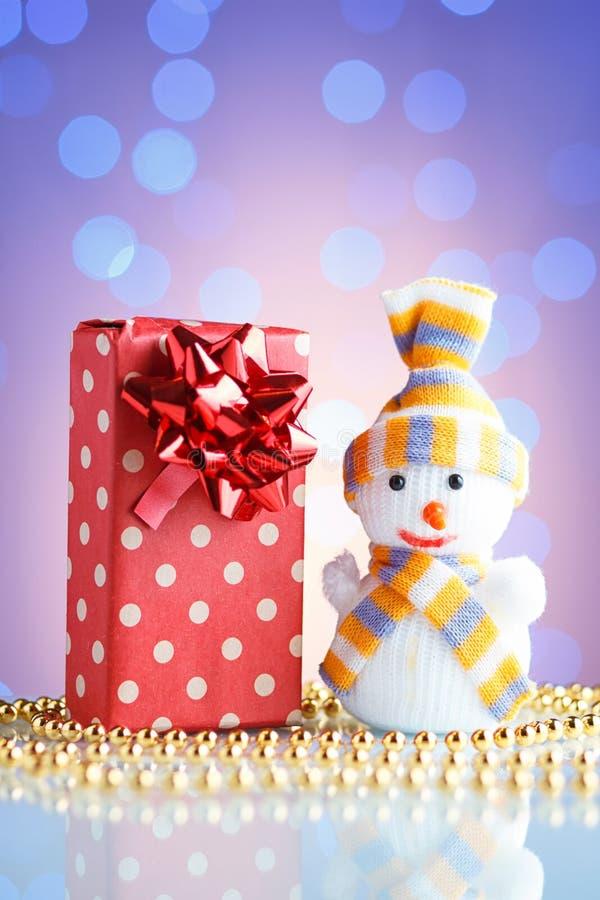 El regalo del Año Nuevo/la Navidad en paquete, las gotas de oro y el muñeco de nieve juegan en una tabla de cristal con un bokeh  imagen de archivo