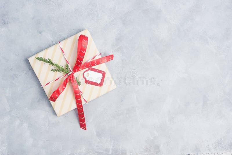 El regalo plano del christma de la opinión superior de la endecha withred la cinta una etiqueta en blanco en la tabla concreta gr imagenes de archivo