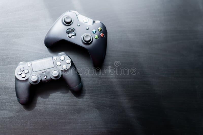 El regulador de Xbox y de Playstation se sent? uno al lado del otro en un fondo oscuro foto de archivo