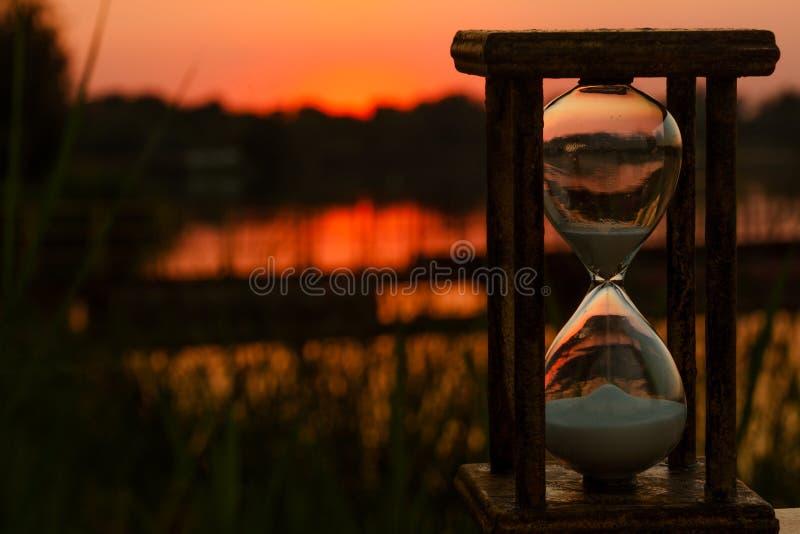 El reloj de arena cuenta abajo del tiempo en la charca de la puesta del sol fotografía de archivo