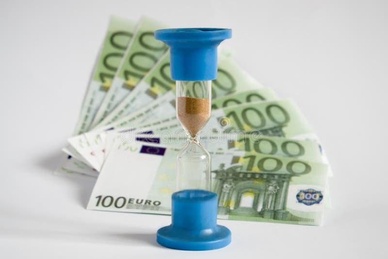 El reloj de arena muestra el equilibrio entre el dinero y el tiempo fotografía de archivo libre de regalías