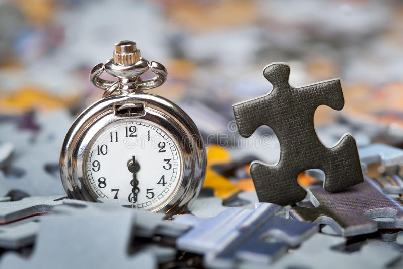 El reloj de bolsillo en una pila de rompecabezas junta las piezas fotos de archivo libres de regalías