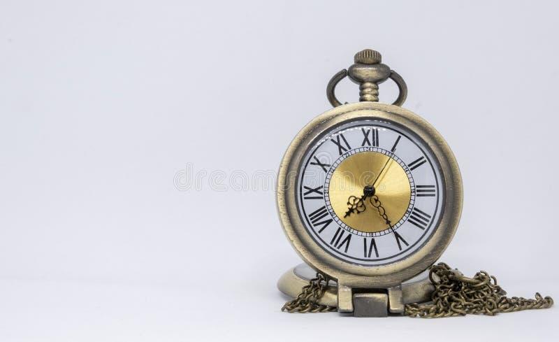 El reloj de bolsillo viejo es un collar situado en el piso blanco que es separado imagen de archivo libre de regalías