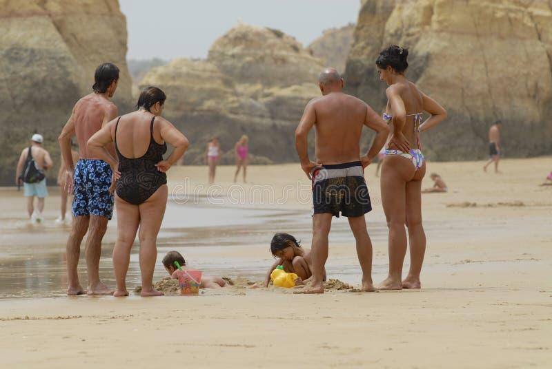 El reloj de la gente embroma jugar en la playa en Portimao, Portugal foto de archivo libre de regalías