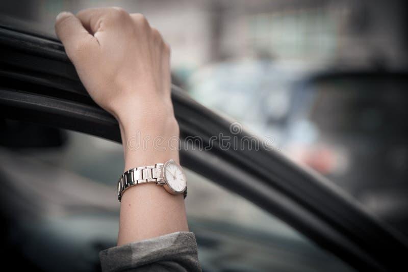 El reloj de las mujeres en la mano de la muchacha Muchacha a toda prisa, coloc?ndose en un atasco El tiempo es oro El hombre pier fotos de archivo
