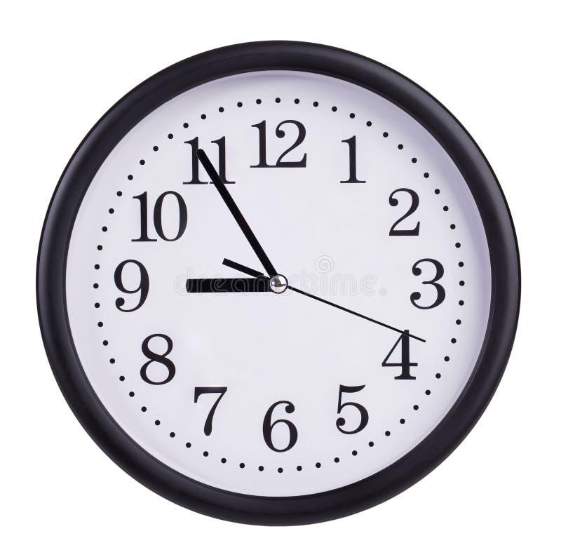 El reloj de pared redondo muestra cinco a nueve foto de archivo