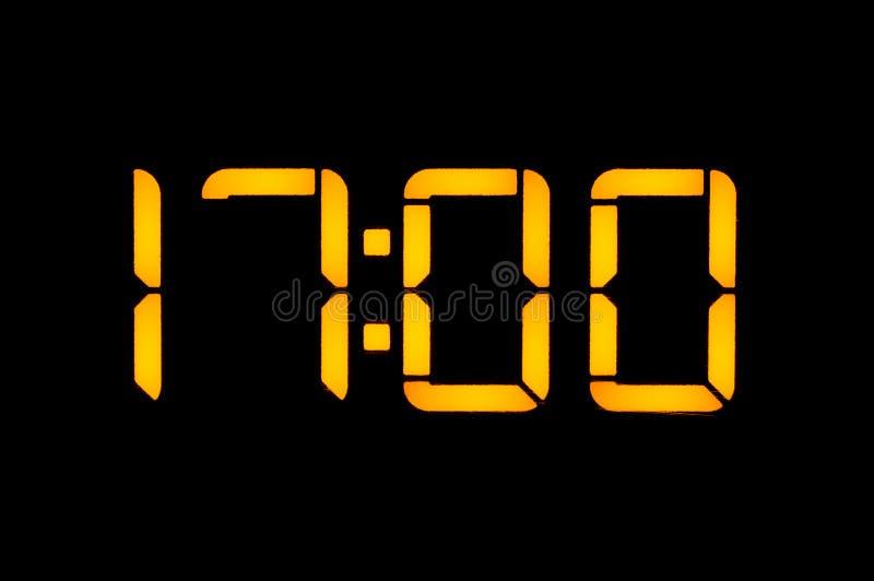 El reloj digital electrónico con números anaranjados en un fondo negro muestra el tiempo Las diecisiete cero de la tarde aislante imagen de archivo