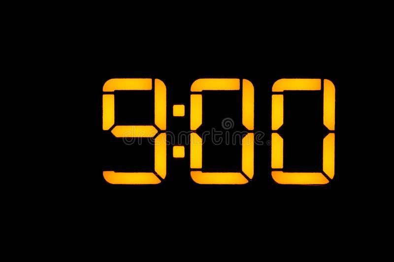 El reloj digital electrónico con números anaranjados en un fondo negro muestra a tiempo nueve horas de cero en la mañana Aislante fotografía de archivo