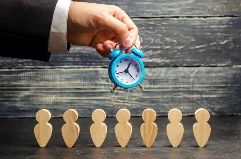 El reloj en las manos de un hombre de negocios y de un equipo En horas extras eficacia del trabajo del aumento Reducción del cost fotografía de archivo libre de regalías