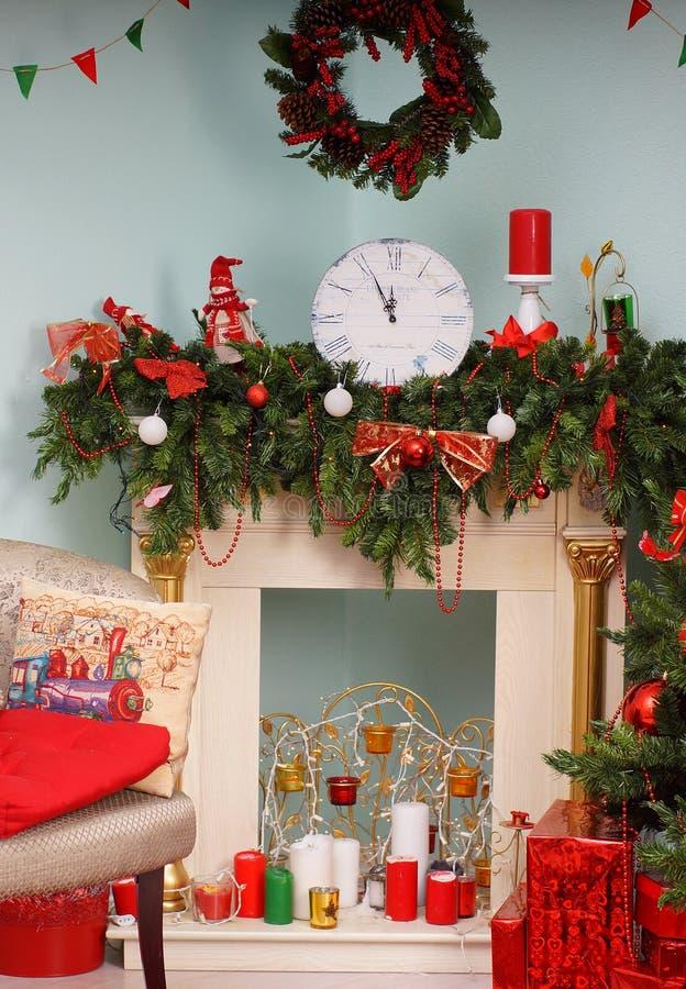 El reloj muestra en cinco minutos a doce en la chimenea, adornada al Año Nuevo imagen de archivo