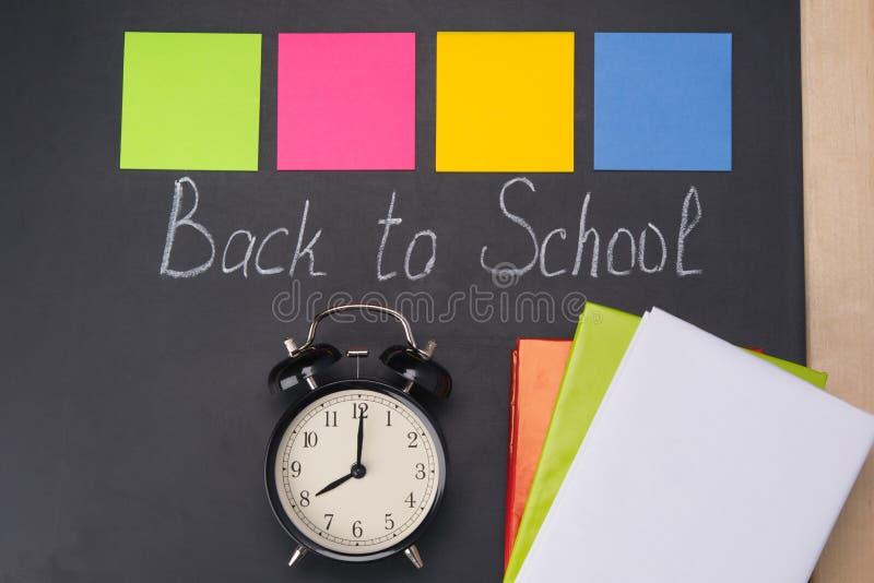 El reloj muestra el tiempo, y encendido remata la inscripción - él tiempo del ` s a la escuela, escrita tiza en un tablero negro fotos de archivo libres de regalías