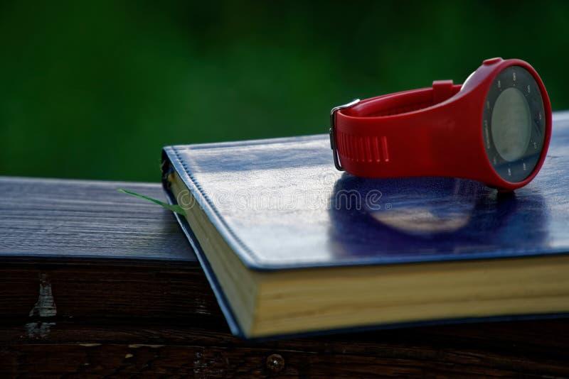 El reloj rojo del deporte en el cuaderno miente en la barandilla de madera en el parque, concepto del negocio fotos de archivo libres de regalías